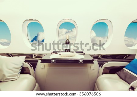 Luxury interior in bright colors of genuine leather in the business jet, sky and clouds through the porthole - stock photo