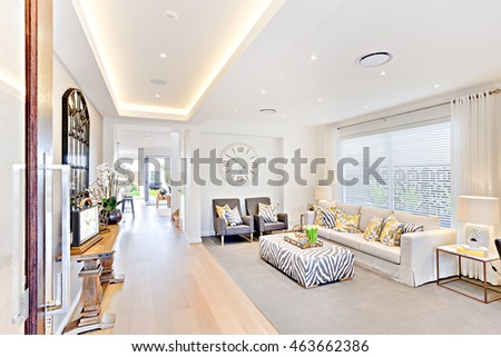 Luxury interior of a living room and a hallway  to the outside, there are old wooden tables, windows, clocks with fancy vase from the left side, modern sofa and pillows with wall watch and a curtain