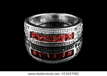 Luxury jewelry. White gold or silver engagement ring with colored gemstone closeup on black background. Selective focus. - stock photo