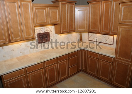 Luxury kitchen in an upscale house with maple cabinets and tile counter tops and floors.