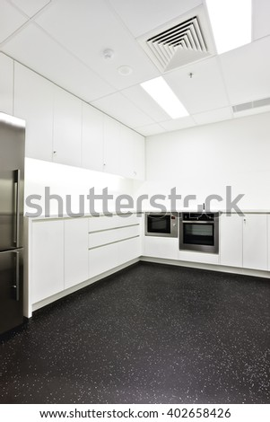 Luxury kitchen included silver ovens attached to wall cabinets with white walls and black floor tiles - stock photo