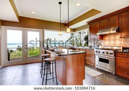 Luxury kitchen interior with green walls and stone floor and water view. - stock photo