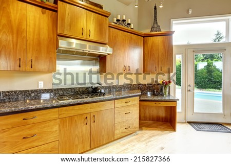 Luxury kitchen room with honey wooden cabinets and black granite tops - stock photo