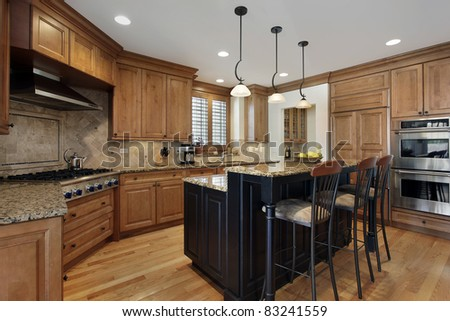 Luxury kitchen with granite island and wood cabinetry - stock photo