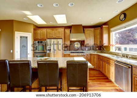 Luxury kitchen with SS-appliances and kitchen island with black leather chairs