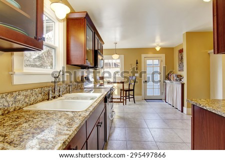Luxury kitchen with tile floor, and stained cabinets.