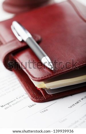 Luxury leather personal organizer with pen on white office desk. Shallow focus.