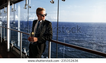 Luxury life. Portrait of the handsome and rich man. Shot from cruise liner. Sea on the background with copyspace - stock photo