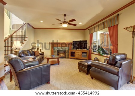 Luxury Living Room Interior With Fireplace And Carpet Floor Black Leather Sofa Armchairs