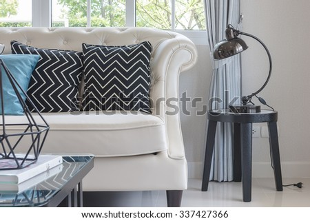 luxury living room with pillows on classic style sofa and lamp on table side - stock photo
