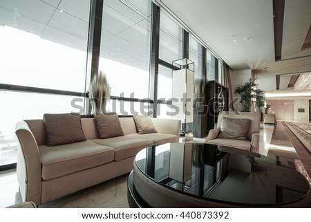 Luxury lobby interior.With crystal lamp,big hall, carpet, french sash,mosaic tile,comfortable sofa, reception desk and long Escalators. - stock photo