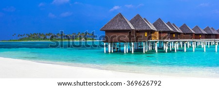 luxury Maldives vacation - panorama with water bungalows - stock photo