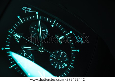 Luxury mens Chronograph Watch, clock deal with blue green illumination. Close-up blue toned studio photo with selective focus - stock photo