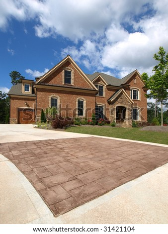 Luxury Model Home Exterior stone driveway with cloudy sky - stock photo