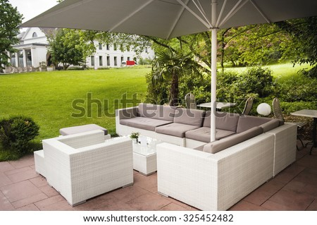 Luxury modern fashioned patio cafe lounge with umbrella and comfotable chairs in green park - stock photo