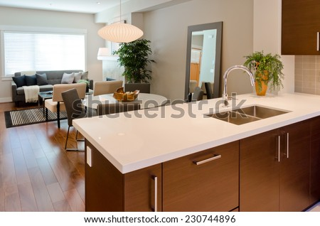 Luxury modern kitchen with dining room and living room at the back. table. Interior design of a brand new house. - stock photo