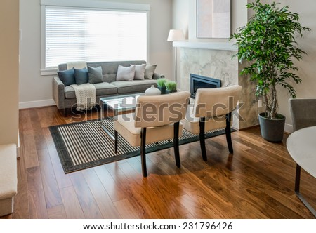 Luxury modern living suite, room with sofa and chairs and nicely decorated with vase coffee table. Interior design of a new house. - stock photo