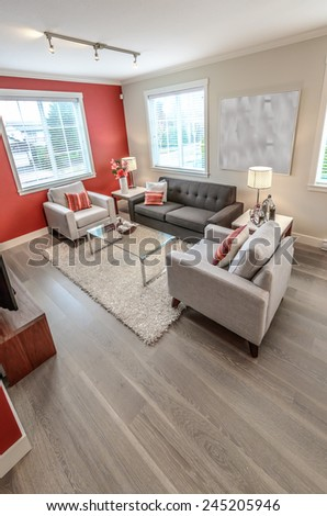 Luxury modern living suite with red color walls, room with sofa and chairs and nicely decorated with vase coffee table. Interior design of a brand new house. Vertical. - stock photo