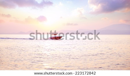 Luxury motorboat on the sea in mild pink sunset light, active lifestyle, expensive water transport, summer vacation, speed and freedom concept - stock photo