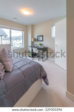 Luxury nicely decorated modern bedroom with some elements of den, home office with the table and the office chair at the back. Interior design of a brand new house. Vertical. - stock photo