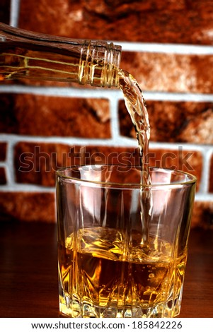 Luxury old whiskey glass on brick wall background - stock photo