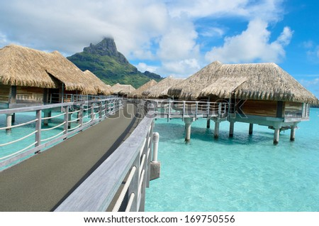 Luxury overwater bungalows in a vacation resort in the clear blue lagoon with a view on the tropical island of Bora Bora, near Tahiti, in French Polynesia. - stock photo