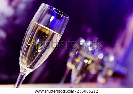 Luxury party champagne glass in nightclub neon lilac, blue and purple lights. Blurry closeup. - stock photo