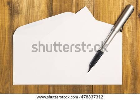 Luxury pen with blank white card and  envelope on wood background, vintage