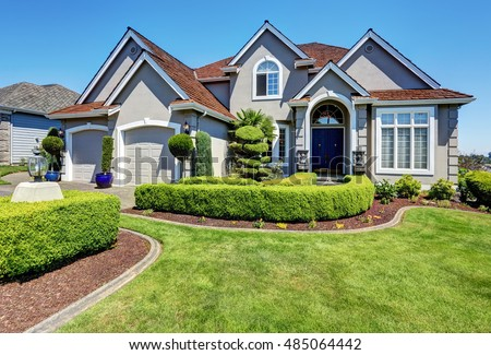 Luxury residential house with perfectly kept front garden and blue sky background. Northwest, USA