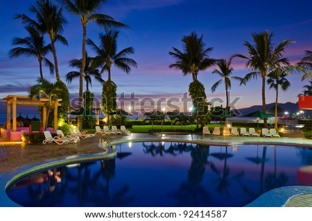 luxury resort with beautiful pool and fantastic ocean view at night - stock photo