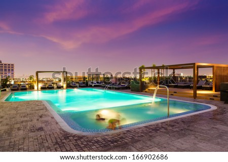 Luxury rooftop swimming pool at sunset, blurred motion - stock photo