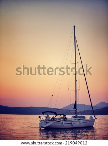 Luxury sailboat in the sea in beautiful sunset light, interesting summer adventure, romantic date on the water, travel and tourism concept - stock photo