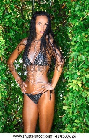 luxury sexy young woman in bikini with many accessories, chains, and jewelry is posing in the outdoor shower under the water - stock photo