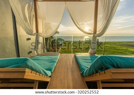 Luxury Spa Wood framed White Curtains Canopy Daybeds (Lounge chairs) Beach Tent on Grass Terrace near island Beach under Golden Sky Sunset in sea horizon in Summer in Resort at Pattaya, Thailand.  - stock photo