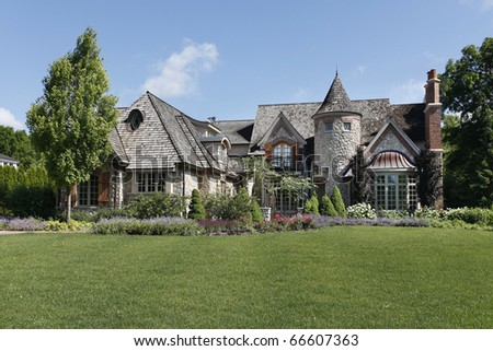 Luxury stone home with turret and cedar roof - stock photo