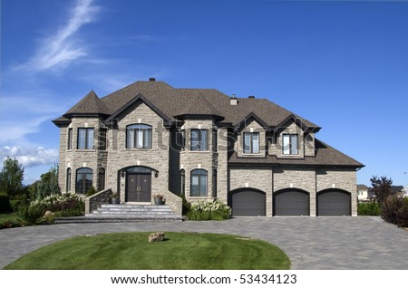 luxury stone house with three garages - stock photo