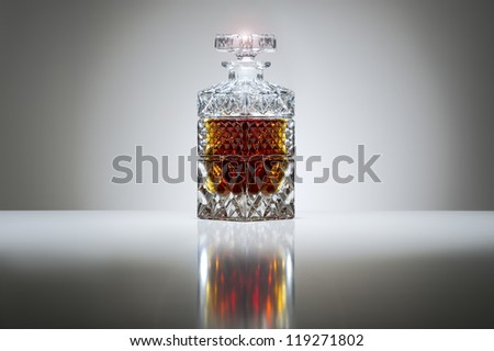 Luxury stoppered cut crystal decanter filled with whiskey or brandy on a graduated grey background with highlight and reflection - stock photo