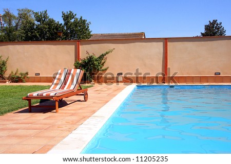 luxury swimming-pool and a deck chair along