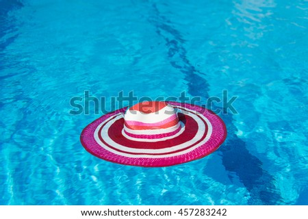 Luxury swimming pool with pink female sun hat - stock photo