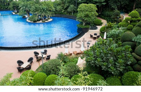 luxury swimming pool with shade trees. - stock photo