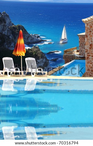 Luxury swimming pool with villa against blue bay - stock photo