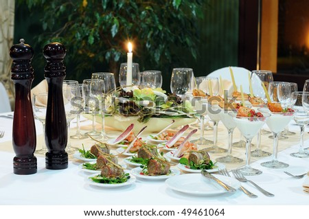 Luxury table setting for a banquet in restaurant. Table with the candle, wineglasses, snacks and cocktails. - stock photo