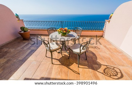 Luxury terrace balcony of exclusive seaside resort with fancy table and chairs fuit and flower bawl and full sea panorama in the beautiful morning lights, Sicily, Italy