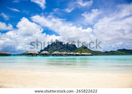 Luxury thatched roof honeymoon bungalows in a vacation resort in the blue lagoon of the Pacific island of Bora Bora, near Tahiti, in French Polynesia.  Villa over water. - stock photo