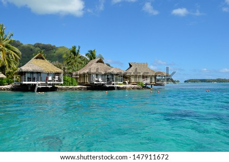 Luxury thatched roof honeymoon bungalows in a vacation resort in the clear blue lagoon of the tropical island of Moorea, near Tahiti, in French Polynesia. - stock photo