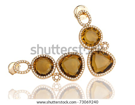 Luxury topaz earring surrounded by shiny diamond - stock photo