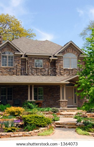 Luxury two-storey house with beautiful landscaping and stone walls - stock photo