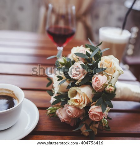 luxury wedding bouquet of tiny roses  laying on wooden table in cafe between coffee cappucino and glass of vine, film like colors