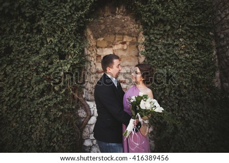 Luxury wedding couple hugging and kissing on the background gorgeous plants, cave near ancient castle - stock photo