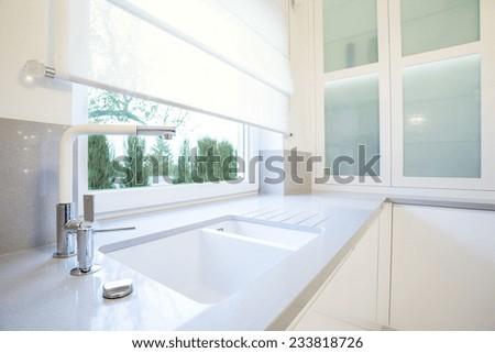 Luxury white kitchen with big window overlooking the garden - stock photo